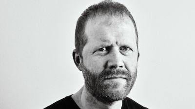 En svartvit porträttbild av Andreas Malm, som tittar in i kameran med allvarsam blick.