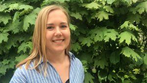 jannica lindqvist i blåvitrandig skjorta framför en lövbuske
