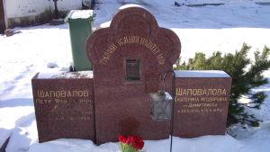 Gravsten med kyrillisk skrift. Snö på marken. Pjotr Sjapovalovs grav i Helsingfors