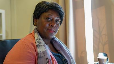 Honorette Muhanzi tittar in i kameran. Hon sitter inomhus.