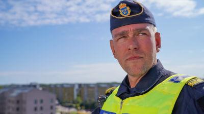 Polisinspektör Jonas Berg på ett tak ovanför ett bostadsområde.