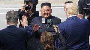 Nordkoreas ledare Kim Jong-un ler brett framför kamerorna.