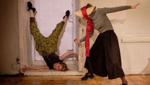Tanssija Annatuuli Saine seisoo päällään oviaukon syvennyksessä. Kati Outinen kumartuneena hänen puoleensa, olkihattu päässään.