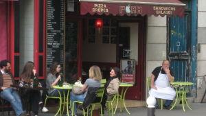 Asiakkaita kahvilan terassilla Pariisissa.