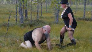 Kari Tykkyläinen kontillaan metsässä, nainen dominana vierellä