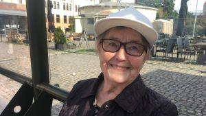 äldre kvinna med vit keps sitter i busskuren och väntar på en buss och ler mot kameran