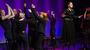 En grupp unga svartklädda kvinnor dansar på en teaterscen. Längst till höger står en kvinna i svart klänning på en stol.