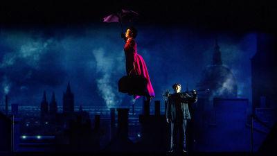 En kvinna i röd klänning svävar iväg mot en natthimmel buren av sitt paraply.