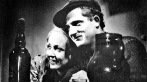 Hymyilevät mies ja nainen nojaavat toisiinsa. Kuva elokuvasta L'Atalante.