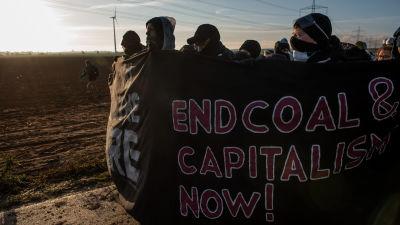 """Andreas Malm och en grupp andra människor ute på en klimataktion. Gruppen har masker framför ansiktet och står invirade i en banderoll med budskapet """"End coal & capitalism now!"""""""