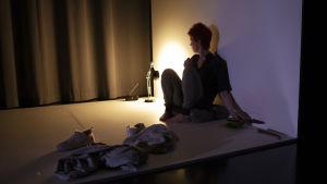 Minna Haapkylän näyttelemä Iina istuu yksin hämärän huoneen lattialla.