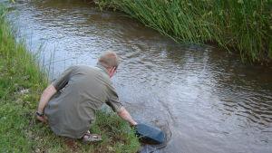 Magnus Dahlbacka hämtar vatten i floden.