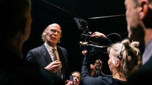Vesa Vierikon näyttelemä Ben Zyskowicz kuvassa miettiväisenä. Videokamera kuvaa häntä, muita hahmoja epäselvinä ympärillä.