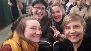 En bild på människor som sitter i en biosalong och ler mot kameran.