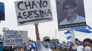 demonstranter håller plakat med bild på dödad pojke Alvaro Conrado
