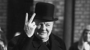 Winston Churchill gör leende v-tecknet iklädd sin höga att.