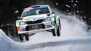 Rallybil hoppar långt i en backe.