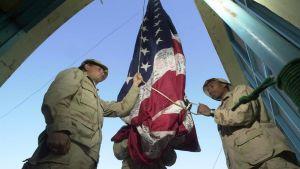Sotilaat nostavat lippua salkoon.