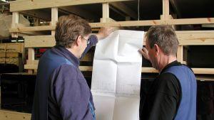 Två arbetare granskar en planritning