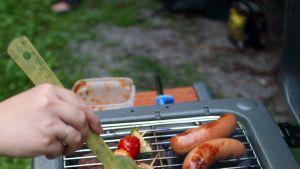 Korv och grönsaker på en utegrill.