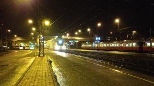 Två tåg på järnvägsstationen i Karis en mörk höstkväll.