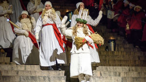 Finlands Lucia 2016 Ingrid Holm iklädd ljuskrona och vit luciadräkt går ner för domkyrkans trappa. Vinkar.