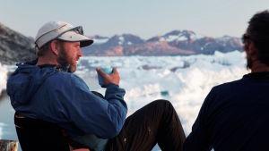 roope roine sitter och dricker te vid en isig strand under en av sina utfärder i vildmarken