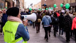 Demonstranter går på Alexandersgatan i Helsingfors. Kvinna talar i en megafon.