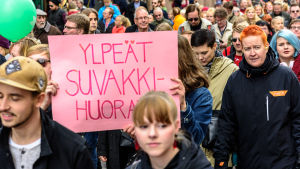 """Demonstranter med en skylt med texten """"Ylpeät suvakkihuorat""""."""