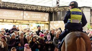 Polis på häst håller ett öga på publik under öppningen av julgatan i Helsingfors.