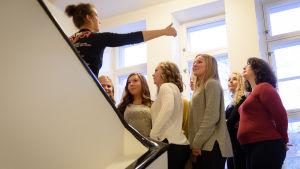 Luciakandidater står i trappuppgång och dirigeras av fotograf för gruppbild.
