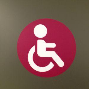 Inva-wc:n luumununaruskea-värinen logo Tohlopin Mediapoliissa