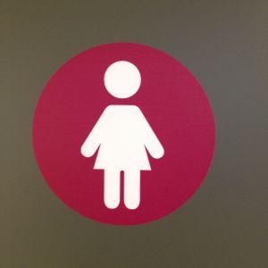 Tohlopin mediapoliin naisten wc:n luumunpunaruskea ja valkoinen logo, nainen pallossa.