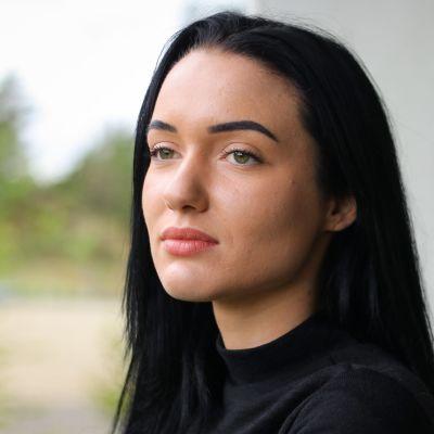 En kvinna med svart hår, står och tittar till vänster.