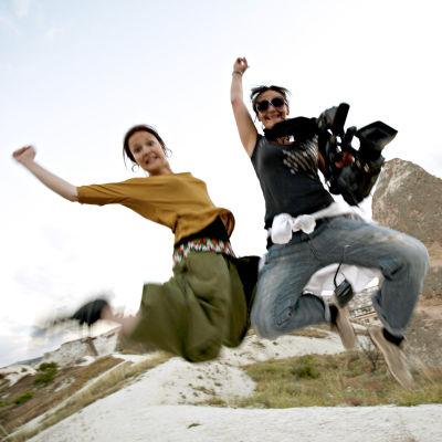 Kuvassa Lotta Kaihua ja Pia Asikainen hyppäävät ilmaan. Naiset kuvaavat Turkissa ohjelmaa Sohvasurffaajat.