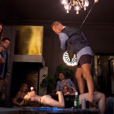Man står mitt under en fest i kalsongerna och skall slå en golfboll ur munnen på en kvinna.