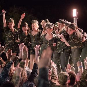 Barden Bellas står på en scen och människor i publiken höjer händerna.