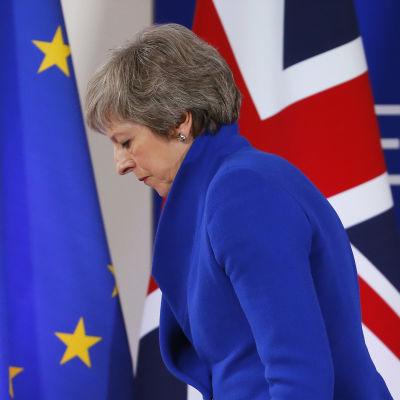 Storbritanniens premiärminister Theresa May framför en EU:s och Storbritanniens flaggor