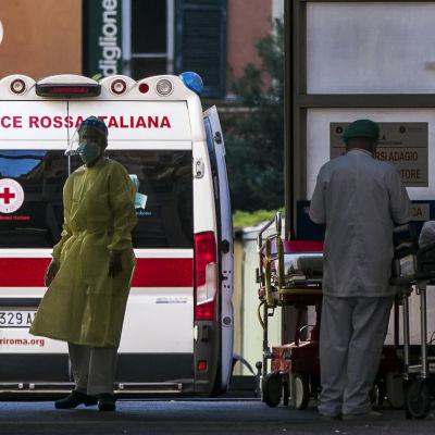 Ambulans och två personer i skyddsdräkt utanför ett italienskt sjukhus.