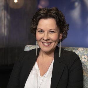 Taiteen moniottelija Krista Launonen Mediapoliksen studiossa kuvattuna, hymyilee iloisesti kuvassa.