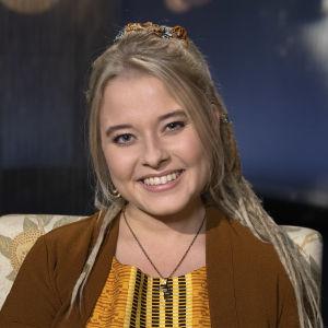 Viola Wallenius kuvattuna Mediapoliksen studiolla Tampereella. Iloinen, hymyilevä Viola ruskeassa villatakissa ja värikkäästä afrikkalaisesta kankaasta ommellussa mekossaan.