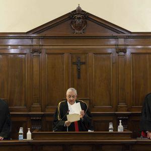 Kolme röyhelökauluksista tuomaria seisoo krusifiksillä varustetun puisen paneelin edessä