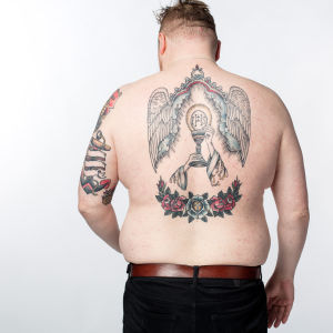 Visa Viljamaa esittelee selkätatuointiaan studiokuvassa.