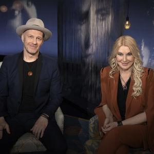Suurlähettiläistä tuttu laulaja, lauluntekijä Jussu Pöyhönen ja työpsykologian tohtori Helena Åhman kuvatttuna Mediapoliksen studiolla, istuvat vierekkäin, Jussulla hattu päässä.