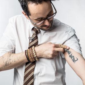 Nicolas Kluger esittelee tatuointejaan studiokuvassa.