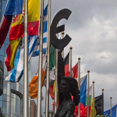 Flaggor på rad i Bryssel, och en Eurosymbol.
