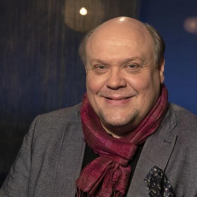 Näyttelijä Hannu-Pekka Björkman Mediapoliksen studiolla Tampereella Anne Flinkkilän vieraana. H-P katsoo kameraan ja hymyilee tyylikäs punainen huivi kaulassaan.