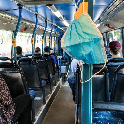 Hengityssuojain roikkuu bussissa.
