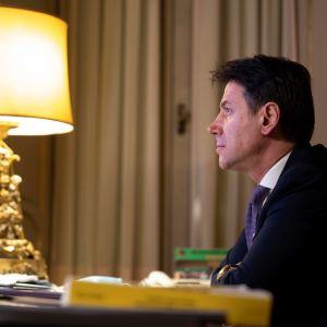 Giuseppe Conte istuu työpöydän ääressä tummassa puvussa, violetissa kravatissa. Pöydällä on lamppu, jolla on korea lampunjalka ja varjostin. Taustalla näkyy verhoja ja ovi, mahdollisesti parvekkeelle.
