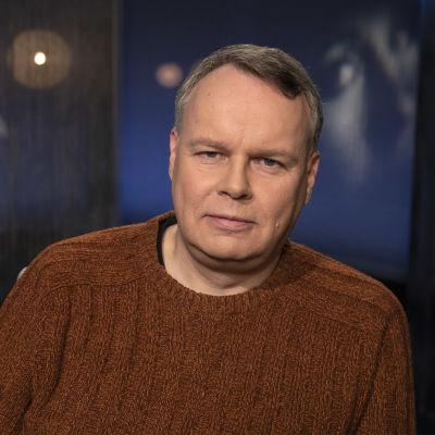Professori Juho Saari Mediapoliksen studiossa Tampereella toimittaja Anne Flinkkilän vieraana, Juho istuu rennosti kuvassa ruskea villapaita yllään.